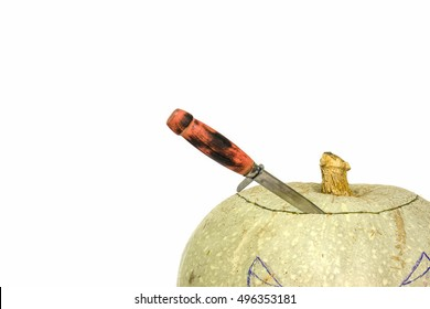 isolated white pumpkin with a knife stuck in the top of the head