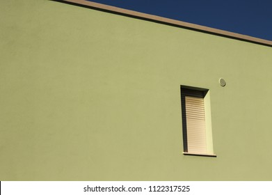 Isolated window in a green wall - Minimal architecture (Fano, Italy)