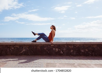 Isolated woman sit on the beach on holidays. Travel and holidays concept. Young woman enjoying summer vacations in the touristic destination Maspalomas. Tourism in spanish Canary islands.