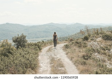 Isolated woman is walking in the countryside pathway (Marche, Italy, Europe)