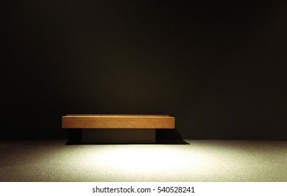 Isolated wood bench in the shadows