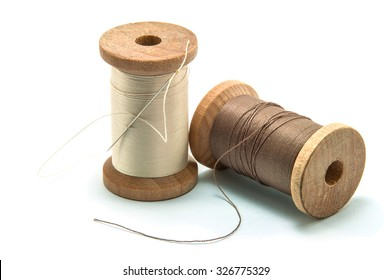 Isolated wooden spool of thread and needle