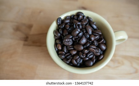 Isolated yellow coffee cup filled with roasted coffee beans against a wood background. Natural light - image