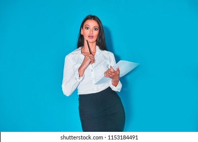 Isolated young business executive brunette woman on blue with white long sleeve blouse and dark skirt.