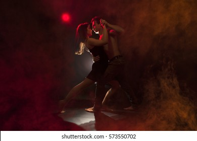 Isolated young caucasian couple dance tango in a dark room with smoke . Red backlight, low key image