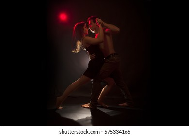 Isolated young caucasian couple dance tango in a dark room . Red backlight, low key image
