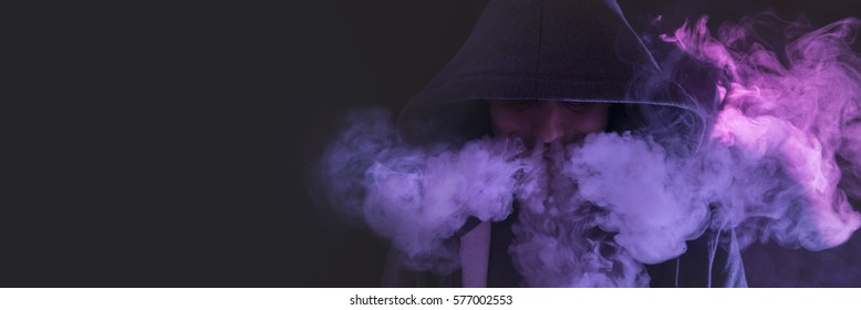 Isolated young man on a dark background holding an electronic cigarette, vaping device, mod, e-cig.