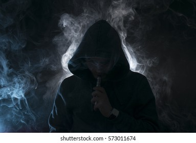 Isolated young man smoking an electronic cigarette on a dark background, holding a vaping device with lots of clouds.