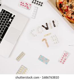 Isolation und bleiben Sie bei zu Hause Konzept mit Coronavirus Tag. Flaches Leadership mit Laptop, Pizza, Pillen und Toilettenpapier