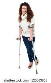 Isolation of a woman walking with help of crutches, full length portrait.