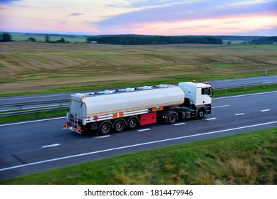Isothermal Tank truck driving on highway. Oil and Gas Transportation and Logistics. Metal chrome cistern tanker with petrochemicals products. Liquid Chemical Freight. Soft focus possible granularity