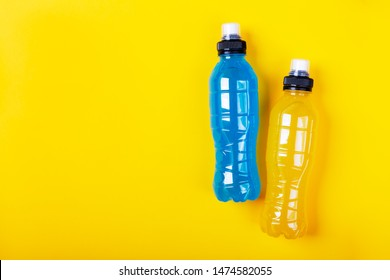 Isotonic energy drink. Bottle with blue and yellow transparent liquid, sport beverage on a colorful background. It usually contains salt and sugar