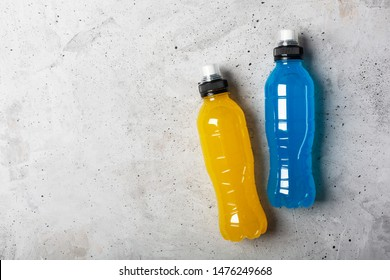 Isotonic energy drink. Bottle with blue and yellow transparent liquid, sport beverage on a gray concrete background. It usually contains salt and sugar and maintains optimal hydration
