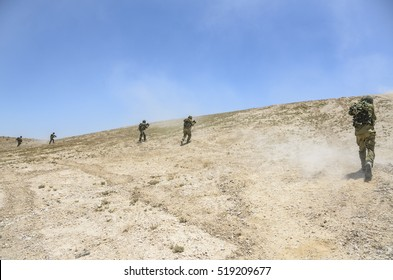 Israel army combat soldiers firing an assault rifle. Infantry soldiers running uphill while firing at enemy targets. Israel army elite unit warriors shooting during military training in the desert.