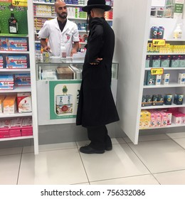 Israel  Bet-Shemesh 2017 August 15. Religious Arab seller in a pharmacy and a religious Jew buyer. Peaceful coexistence concept.