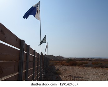 Israel. The border of Israel and Jordan. Jordan River. - 10.05.2015: Flags of Israel and Jordan over the barrage of a minefield. In the background is a Christian temple.