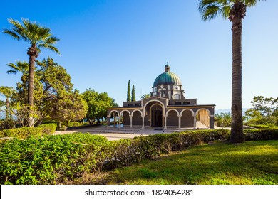 Israel. The Catholic Church of the Beatitudes of the Italian Franciscan monastery on Mount Bliss. The Sea of Galilee. Blooming huge park around the monastery. The concept of religious pilgrimage