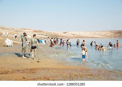 Israel, Dead sea - December 26, 2018: Unidentified People enjoying  Dead sea salty water, swimming and natural mineral mud on the beach