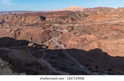 the israel egypt border in the eilat mountains showing an access road that stops at the sinai barrier fence