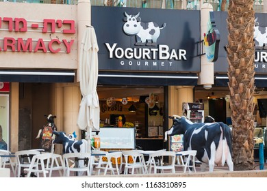 Israel, Eilat, June 2018:sign above the entrance decorative cow near tables on the street near yogurt bar in Eilat