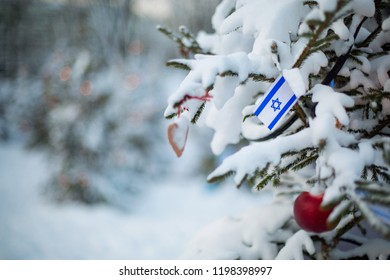 Israel flag. Christmas background outdoor. Christmas tree covered with snow and decorations and Israeli flag. Hanukkah holiday greeting card.