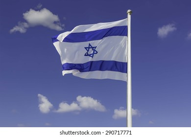An Israel flag flapping in the wind against the blue sky background with  white clouds. The flag is in white and blue colors with the star of David. The flag is posted on a pole high in the sky.