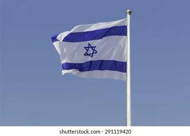An Israel flag flapping in the wind isolated on blue sky background. The flag is in white and blue colors with the star of David. The flag is posted on a pole high in the sky.