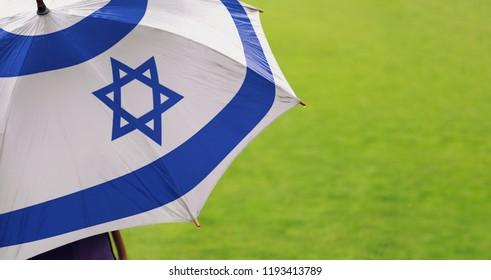 Israel flag umbrella. Close up of printed umbrella over green grass lawn /field. Rainy weather forecast concept.