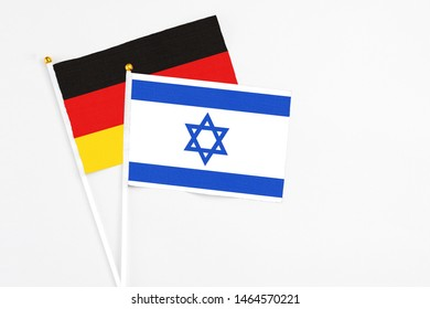 Israel and Germany stick flags on white background. High quality fabric, miniature national flag. Peaceful global concept.White floor for copy space.
