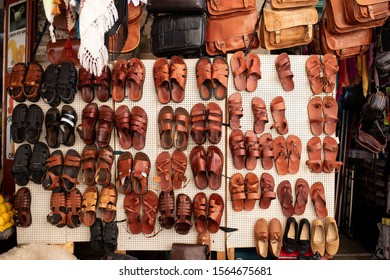 ISRAEL, JERUSALEM- 10 October 2019: leather brown and black sandals and flip flops hanging on one of the stalls, souvenir shop on the streets of the Old City of Jerusalem