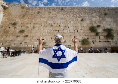 ISRAEL, JERUSALEM - OCTOBER 07, 2014: A man with an Israelian flag and his arms raised in front of the western wall in the old city of Jerusalem