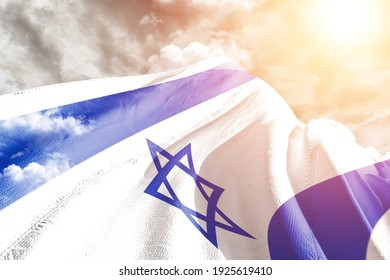 Israel national flag cloth fabric waving on beautiful grey sky.