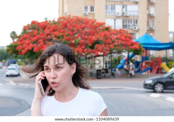 ISRAEL - Netanya, 31 May 2018: girl speaks on the phone beautiful tree