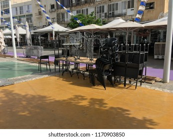 Israel, Netanya, June 2018: Cafe chairs stacked on the street during Shabbat