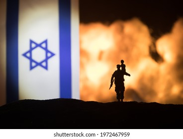 Israel small flag on burning dark background. Concept of crisis of war and political conflicts between nations. Silhouette of armed soldier against a Israel flag. Selective focus
