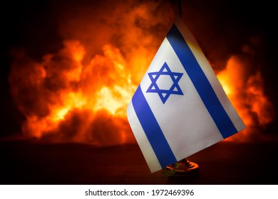 Israel small flag on burning dark background. Concept of crisis of war and political conflicts between nations. Selective focus