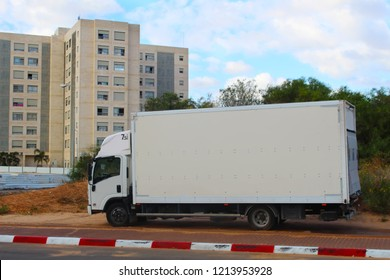 Israel: Truck parked on the side of the road. Border in Red and White Stripes, No Parking Truck in Israel. Modern Apartment Buildings, New District of Rishon LeZion city
