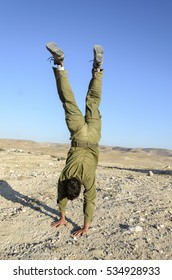 Israeli army combat soldier doing a head stand. Playful soldier standing on his hands during military training in the desert. Infantry soldier displays acrobatic skills in combat training.
