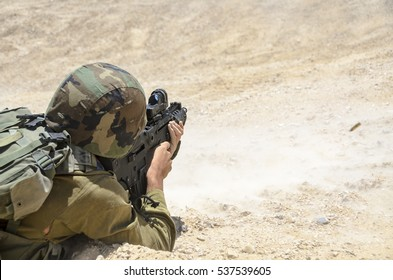 Israeli army combat soldier firing at terror targets. Soldier shooting at enemy targets while laying on the ground. Military training in the desert. Special forces warrior shooting an assault rifle.
