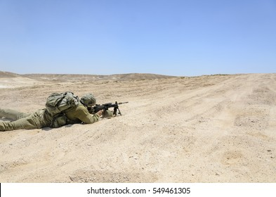 Israeli army combat soldier firing while charging on terror targets. Infantry troop shooting while laying down during military training in the desert. Soldiers aiming at enemy targets while fighting.