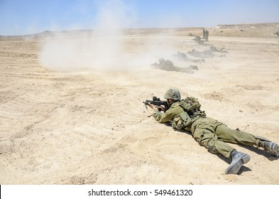 Israeli army combat soldier firing while charging on terror targets. Infantry troops shooting while laying down during military training in the desert. Soldiers aiming at enemy targets while fighting.