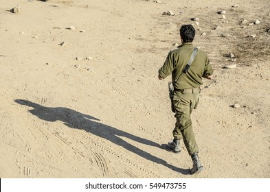 Israeli army combat soldier walking away from camera in desert background. High angle isometric view of Israeli officer with assault rifle walking in day light.