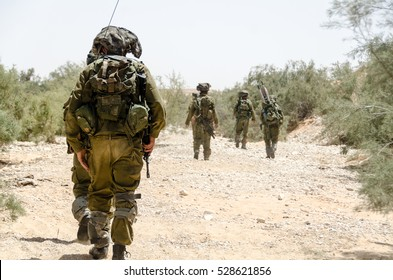 Israeli army combat soldiers return to base after completing military mission during military campaign / war. Desert landscape, armed infantry soldier walking in the foreground. Soldiers walking away.