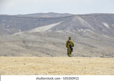 Israeli army lone soldier in the desert. Solitary soldier reflecting in the desert landscape. Armed soldier during military training with an arid desert in the background.