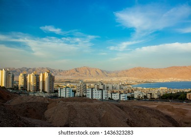 Israeli city Eilat photography foreshortening from above in high outskirts mountain view point with living building and Gulf of Aqaba Red sea bay place in sun rise early morning time