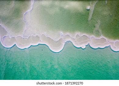Israeli coast of the Dead Sea. salt mushroom  crystals formations, clear cyan green calm water near, typical landscape at Ein Bokek beach, Israel