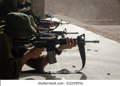 Israeli combat soldier of an elite counter-terror unit aims and shoots M16 assault rifle at in a military shooting range during training for a raid on terror objectives.