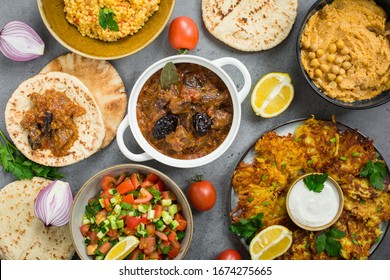 "Israeli cuisine: esik fleisch - beef stew with damson plums and spices, hummus,  potato latkes, ptitim, a type of pasta also known as ""Israeli couscous"", pita bread, israeli salad. Grey background."