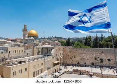 An Israeli flag blows in the wind as jewish orthodox believers read the Torah and pray facing the Western Wall, also known as Wailing Wall or Kotel in Old City in Jerusalem, Israel.