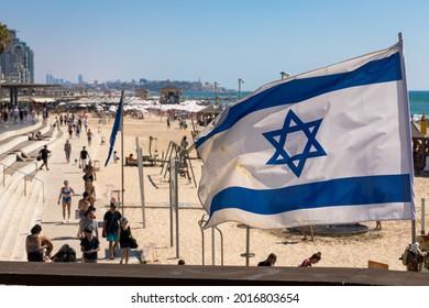 Israeli flag fluttering over Tel Aviv Embankment with old Jaffa view on background